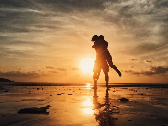 Silhouette of couple embracing while standing at beach against sky during sunset