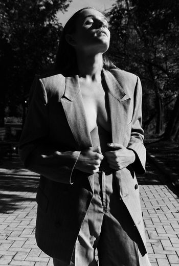 Young woman with eyes closed standing on footpath during sunny day