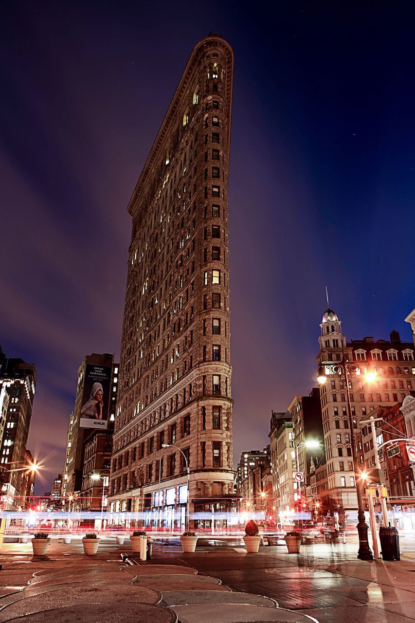 architecture, illuminated, building exterior, night, built structure, city, street, sky, city life, skyscraper, outdoors, street light, transportation, road, travel destinations, low angle view, large group of people, cityscape, modern, people