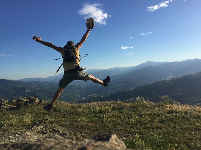 Rear View Of Playful Man Jumping On Mountains Against Sky