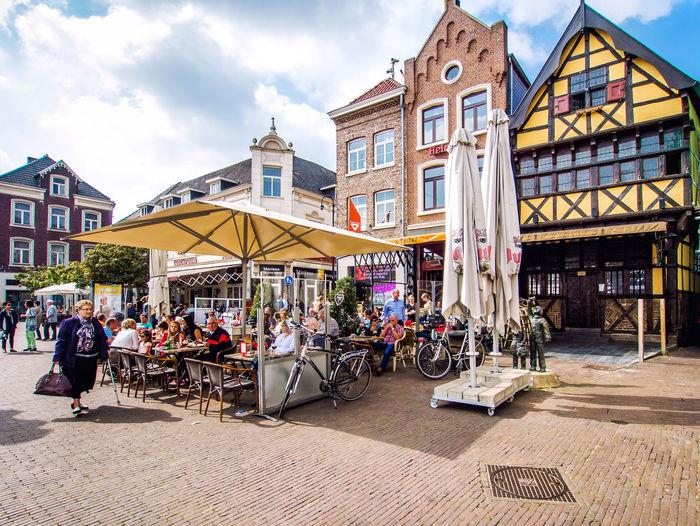 People at sidewalk cafe in city against sky
