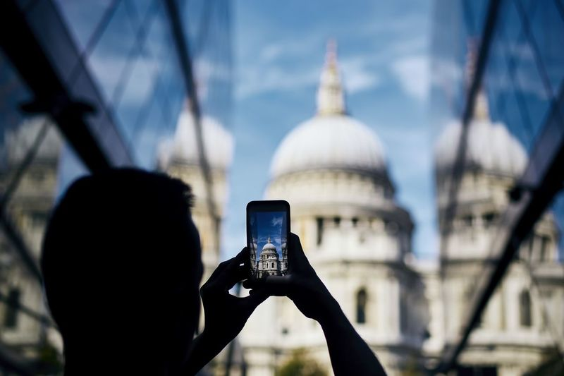 Rear view of man photographing through smart phone