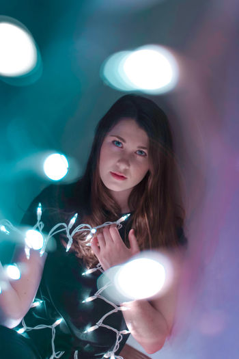 Portrait of young woman holding illuminated lights