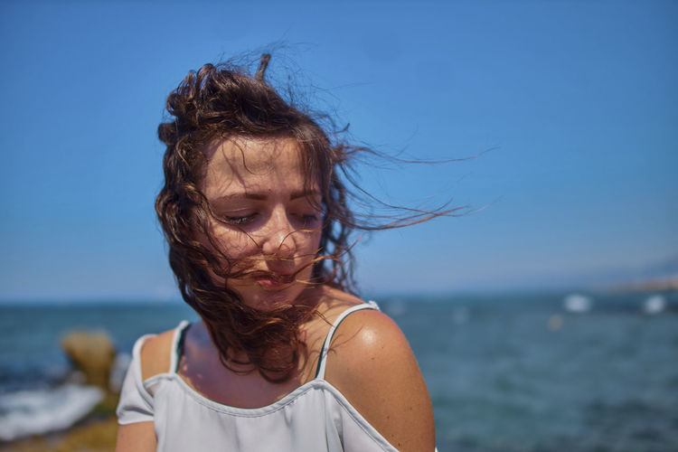 Close-up of young woman with tousled hair against sea and clear sky