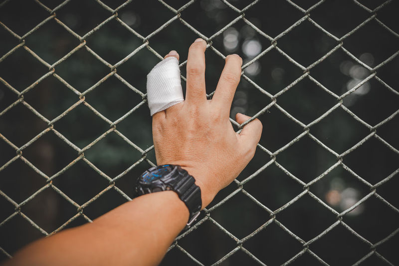 Cropped hand of man holding chainlink fence