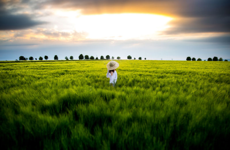 Side View Of Woman Standing Amidst Plants Against Sky During Sunset