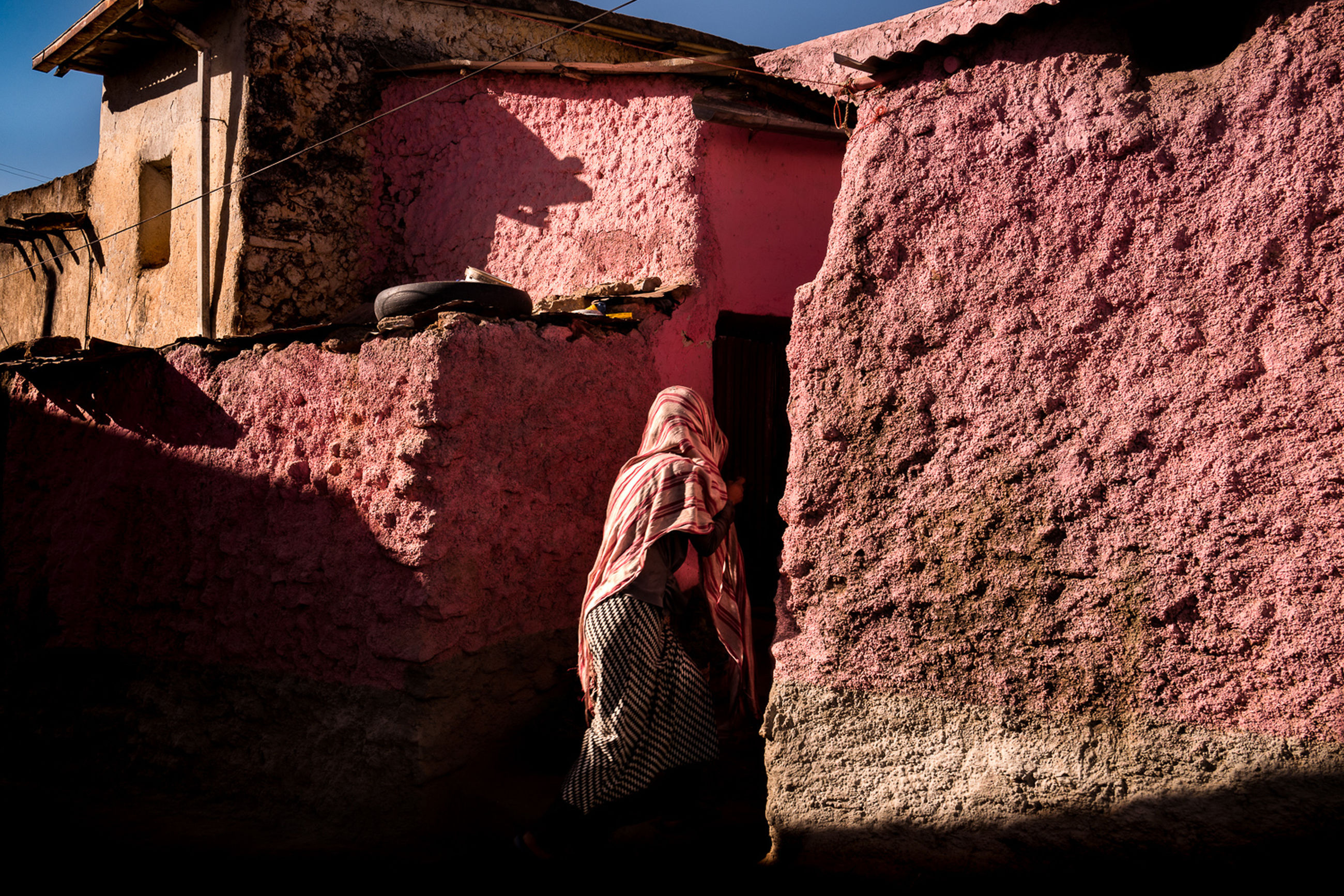 built structure, architecture, building exterior, day, sunlight, clothing, textile, nature, no people, building, rear view, wall - building feature, wall, outdoors, shadow, drying, house