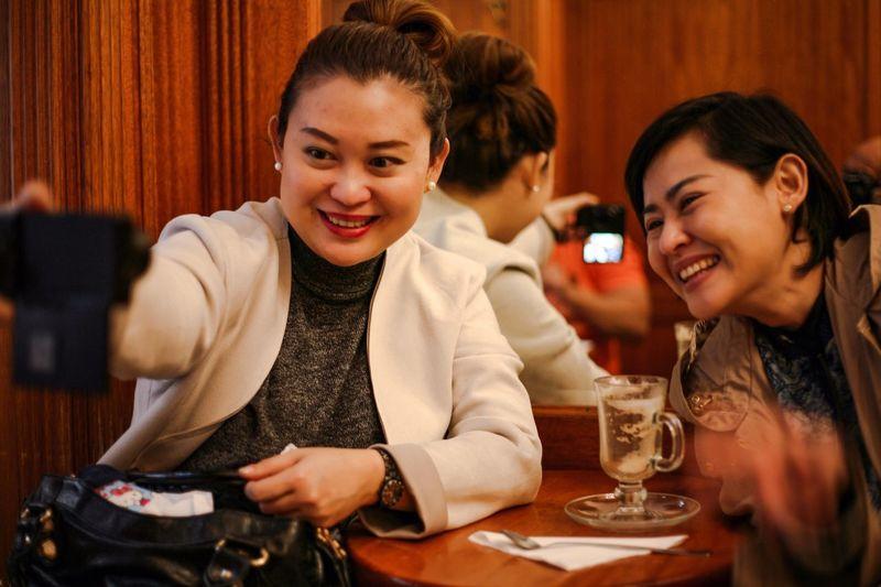 Happy Women Talking Selfie Using Phone In Restaurant
