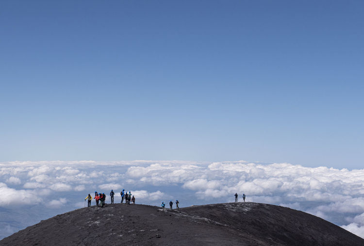 People standing on mountain against cloudy sky
