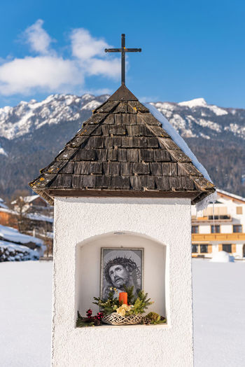 The mountain chapel with cross covered with wooden shingle. snow-capped mountains, blue sky