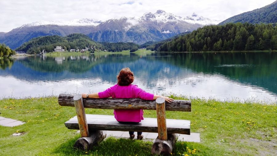 Rear view of woman sitting on bench at lakeshore against mountains