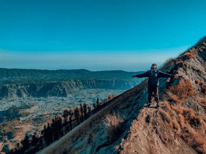 Man standing on rocks against blue sky