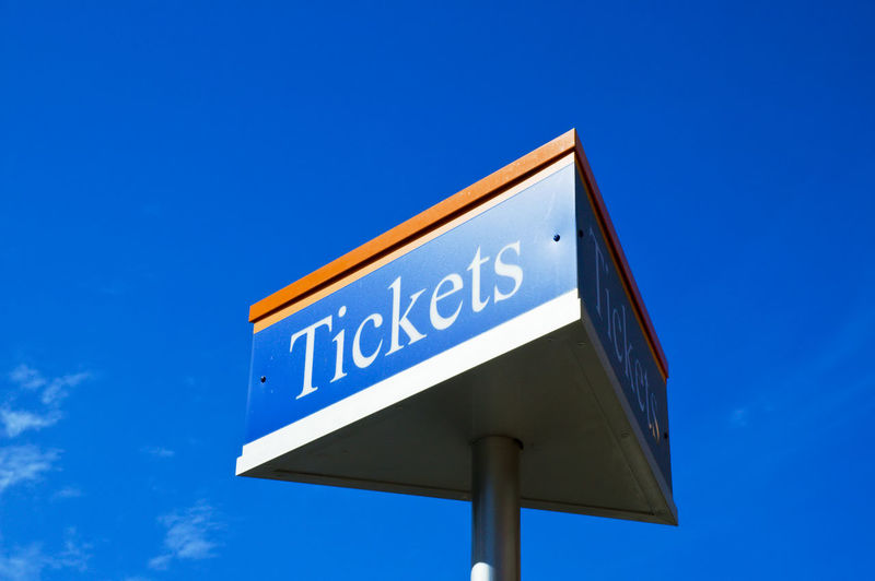 Low Angle View Of Tickets Text On Metallic Pole Against Blue Sky