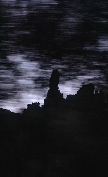 Silhouette rocks on shore against sky at dusk