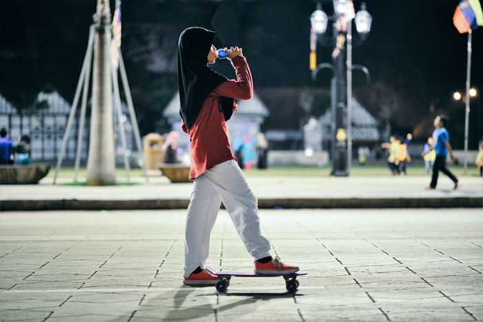 Side view of teenage girl drinking while standing with skateboard on footpath in park at night