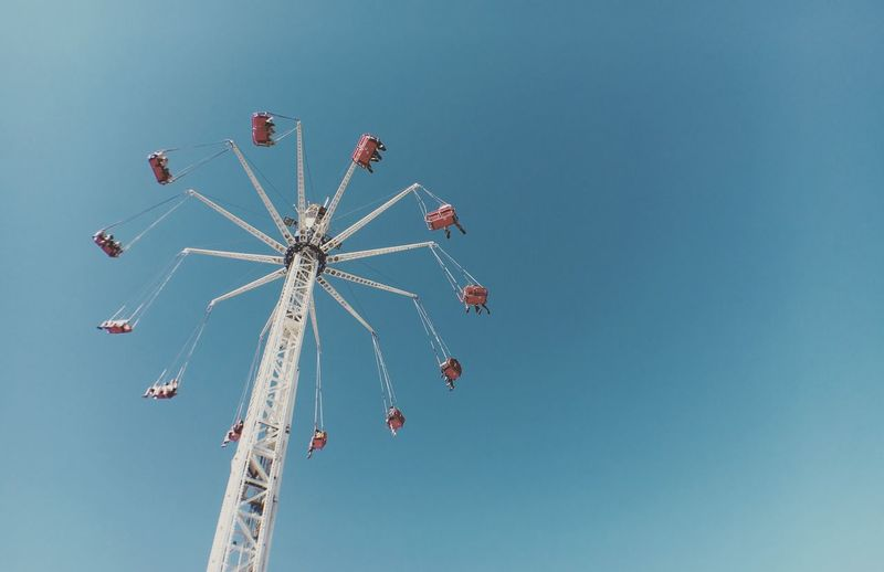 Low angle view of chain swing ride against clear sky at coney island