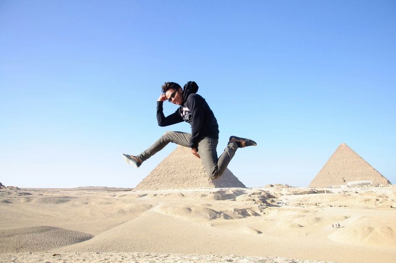 Young man wearing hooded shirt and sunglasses in mid-air at giza pyramids against clear sky