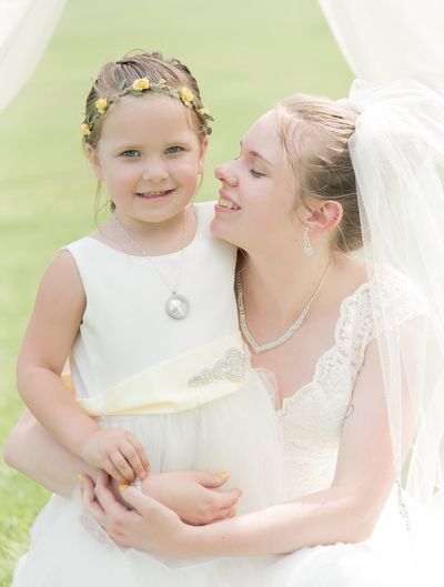 Bride Beginnings Life Events Togetherness Mother Pregnant Love Bride Anticipation Two People Wedding Dress Wedding Real People New Life Standing Day Happiness Lifestyles Bonding Young Women Young Adult and flower girl wedding