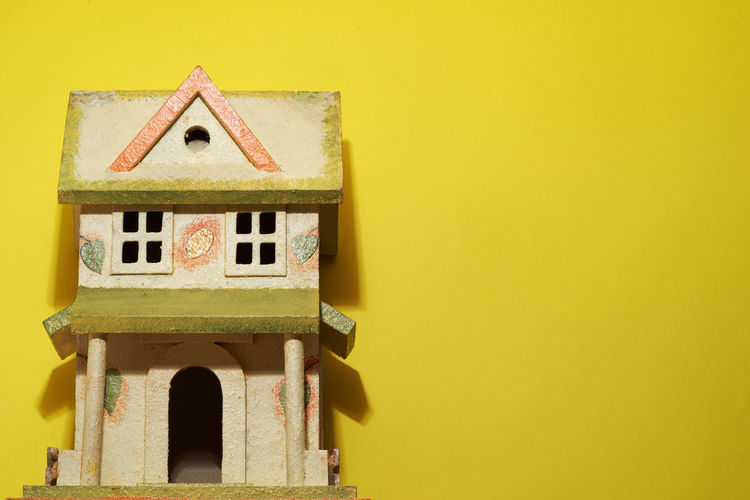 Close-up of birdhouse against yellow wall of building