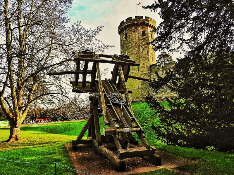 1200s Castle Close Up Fire Flag Green Grass Historic Historical Building History No People Old Buildings Outdoors Tower Trebuchet Trees Warwick Warwick Castle Warwickshire Weapon Wood