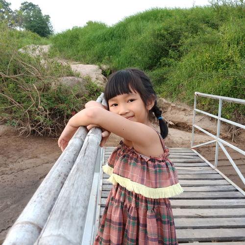 Side view portrait of girl standing on footbridge