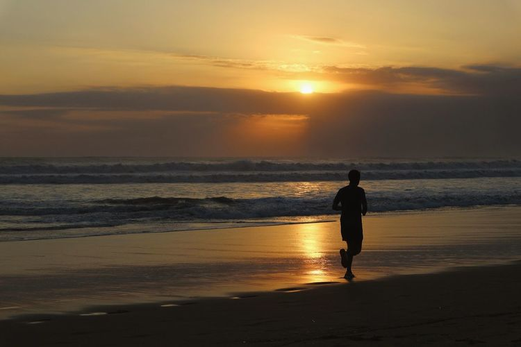 Sunset jogger. Colorful Photography Travel Destinations Paradise Idyllic Bali Tranquility Worlds Best Beaches Vacations Tropical Climate Worlds Best Sunsets Jogging Jogger Excercise Fitness Running Beauty In Nature Clouds And Sky Wave Sea Sunset Low Tide Beach Silhouette Romantic Sky Seascape Surf Coast Atmospheric Mood Horizon Over Water
