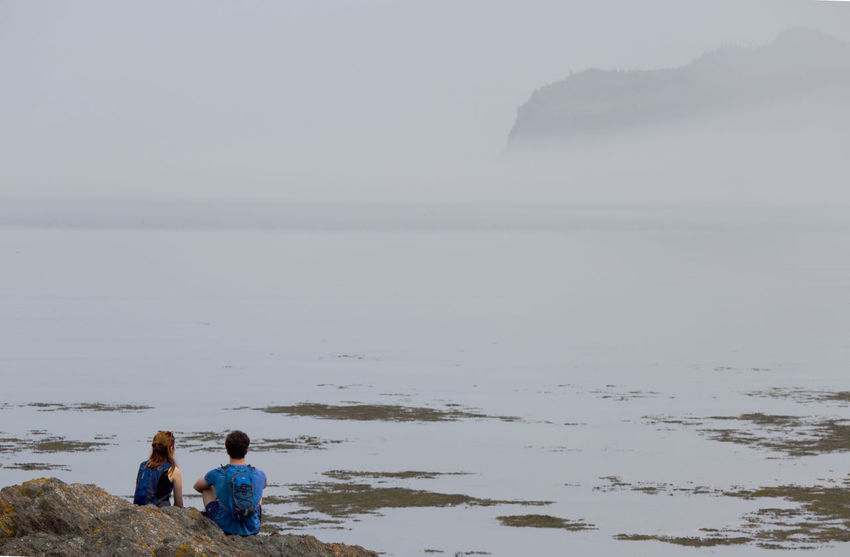 Two people looking at the fog coming in and hiding the mountain at Bic Park Beach Beauty In Nature Bonding Day Fog Friendship Horizon Over Water Leisure Activity Lifestyles Men Nature Outdoors People Real People Rear View Scenics Sea Sky Standing Togetherness Two People Vacations Water Women