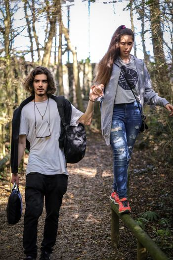A young man supports the hand of a girl walking on wooden rails. Togetherness Two People Young Adult Leisure Activity Happiness Casual Clothing Fun Outdoors Young Women Enjoyment Walking People Portrait Sunny Day SUPPORT Bonding Holding Hands