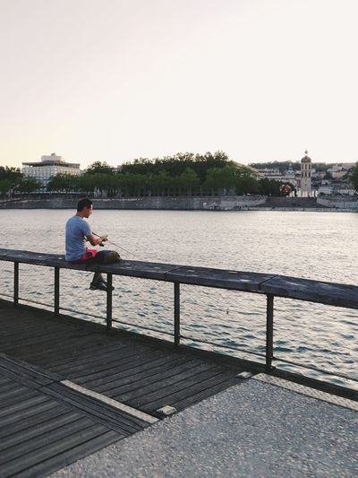 Man sitting on pier by river against clear sky