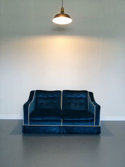 Illuminated Pendant Light Over Empty Sofa In Room