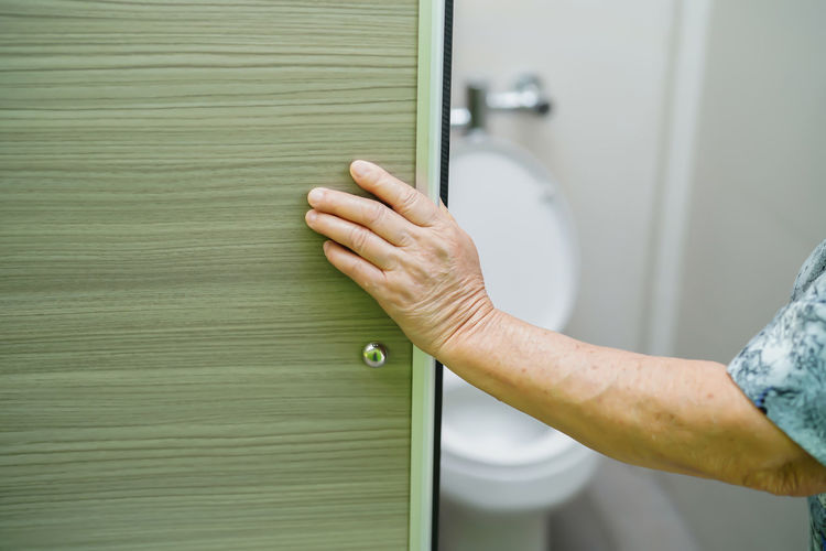 Cropped hand of woman entering bathroom at home