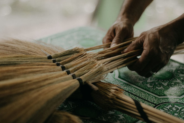 Close-up of person working on handcrafted walis tambo or brooms