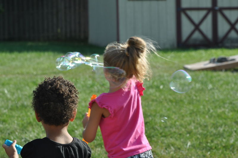 Young Girls Playing with Bubbles Friends Relationship Blond Hair Bubble Bubble Wand Child Childhood Friendship Fun Girls Leisure Activity Nature Outdoors People Play Playing Real People Togetherness