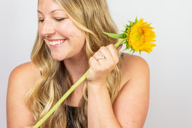 Portrait of a smiling young woman holding yellow flower
