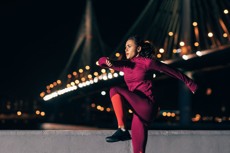 Woman exercising in city at night