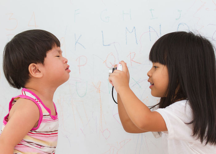 Side view of girl photographing brother crying against wall