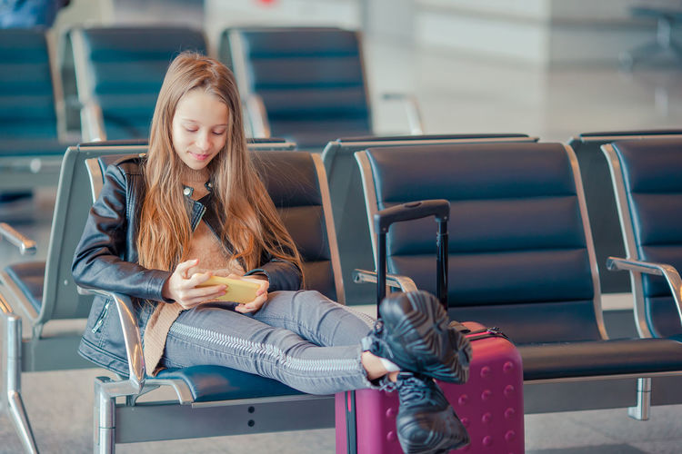 Full length of girl using phone while sitting in waiting room at airport