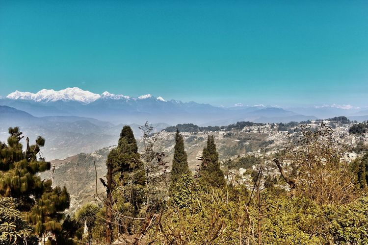 Scenic view of mountains against blue sky in darjeeling / india