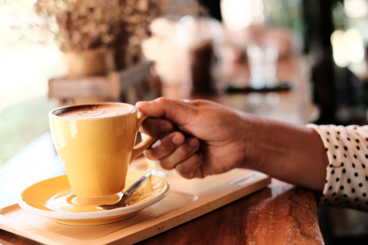 Yellow cup of Hot coffee in break time at cafe , film look effect image tone. Drink Food And Drink Refreshment Coffee Coffee - Drink Table Coffee Cup Cafe Mug Cup Human Hand Saucer Hand Human Body Part Focus On Foreground One Person Adult Latte Hot Drink Frothy Drink Coffee Shop Relax Break Time