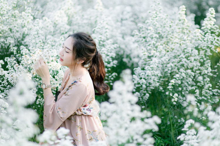 Side view of woman smelling white flowering plant