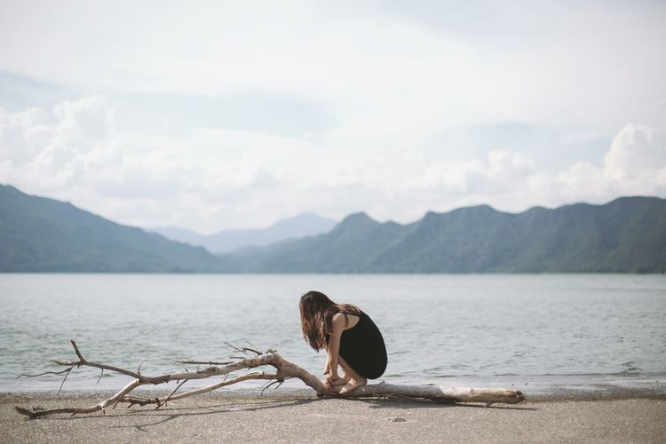 Girl sitting on driftwood log at beach against mountain range