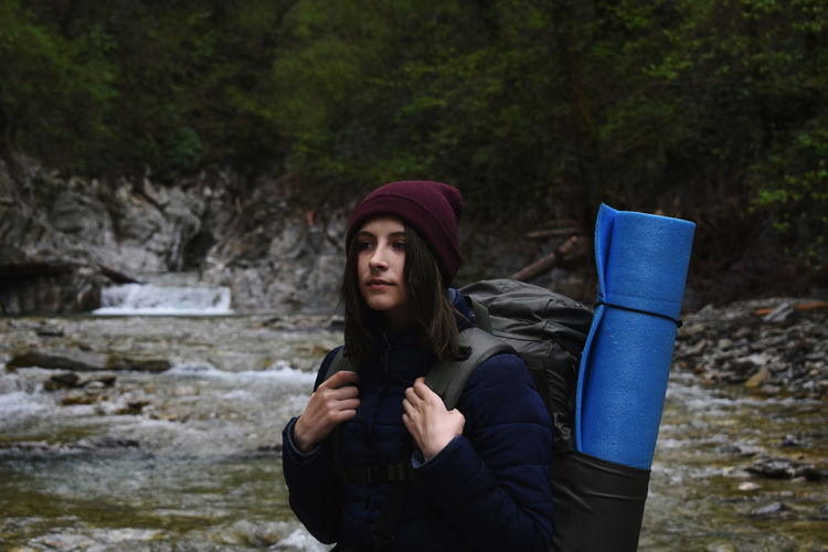 Backpacker walking against stream in forest