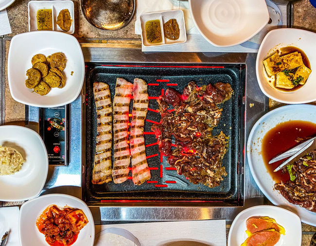 Korean barbecue feast of pork belly, beef bulgogi, and banchan