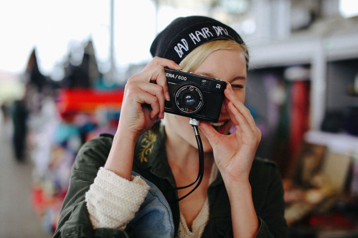 Young woman taking a photo Casual Clothing City Connection Day Focus On Foreground Fun Headshot Holding Leisure Activity Old Camera One Person One Woman Only Only Women People Photography Themes Portrait Portraits Smile Young Adult Young Women