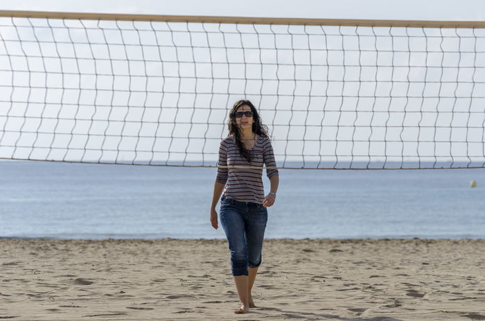 Woman is walking on a beach with casual clothes. It's winter. Alicante, Spain Beach Brunette Calpe Horizon Over Water Mediterranean  Nature Net One Person Sand Sand & Sea Sea Sunglasses Sunlight Vacations Vacations Voleibol Walking War Water Winter Woman Young Adult