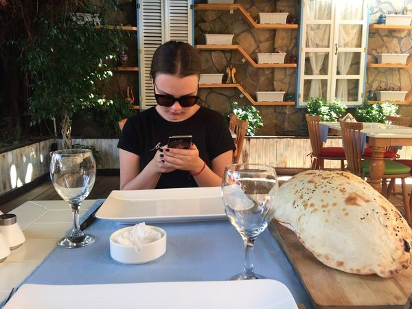 Girl waiting for her food in the turkish restaurant and using mobile phone Bread Cafe Cellphone Dinner Girl Glass Lunch Mobile Phone Pitta Restaurant Sunglasses Table Turkey Waiting Wireless Technology
