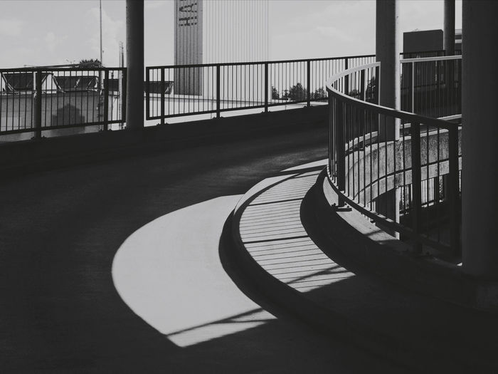 Footbridge over footpath in city against sky