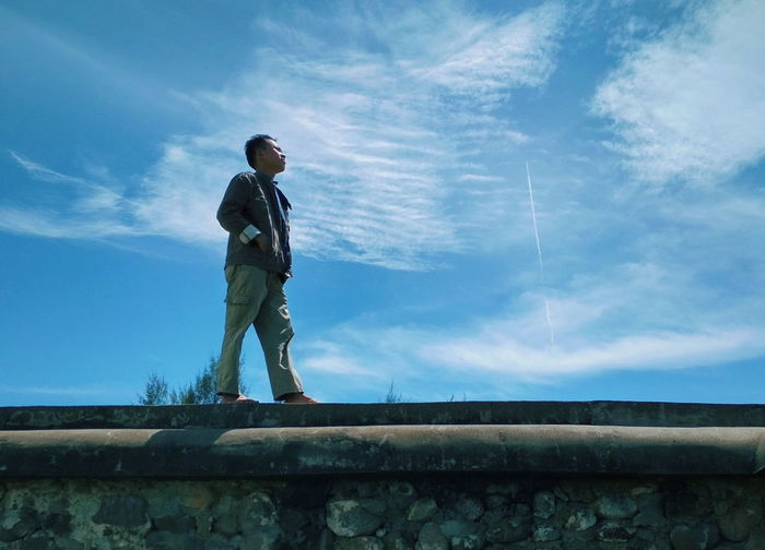 Low angle view of man standing on retaining wall against sky