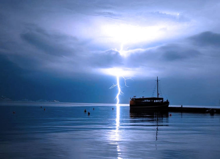 Captured moment Cloud Distant Lightening Lighteningstrikes Sea Ship Sky Tranquility Water