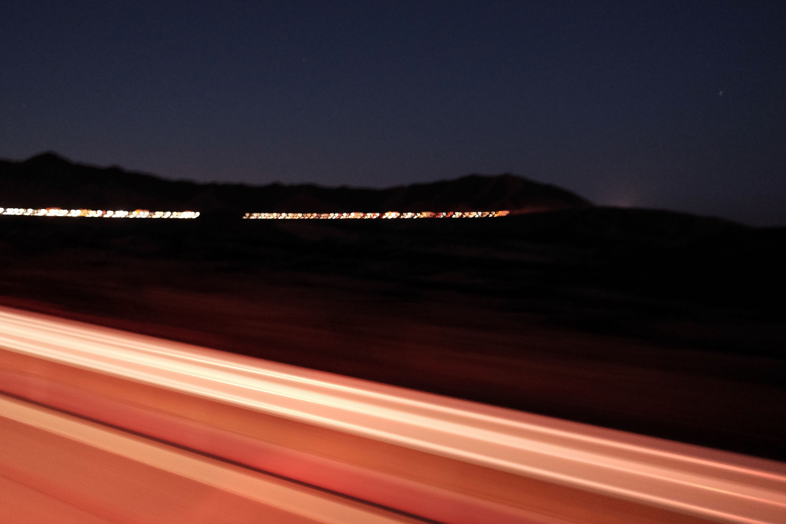 speed, transportation, night, no people, outdoors, motion, sunset, illuminated, nature, sky, scenics, beauty in nature, sea, clear sky, water